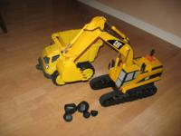 Toy yellow excavator with rocks and an extra truck.