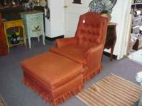 Tufted back arm chair and matching ottoman are skirted