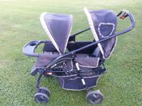 THIS IS A COSCO TWINS STROLLER WITH CANOPIES OVER BOTH
