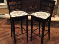 Two barstools. Black wood with metal footrail.  Both