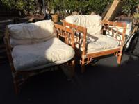 Two rattan chairs with white seating cushions. Very