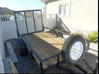 with 5 x 10 flat bed, rear ramp and mounted spare tire.