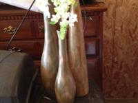 Three different vases with flowers included.