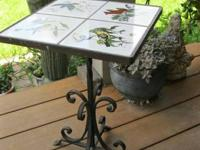 This  vintage iron and tile table features birds,