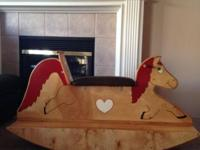 We have a large vintage wooden rocking equine with