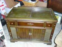 This is an old console stereo cabinet in an antique