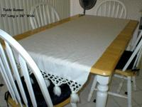 This vintage table runner is white and has tassels on