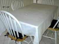 This vintage cloth tablecloth is white and has a design