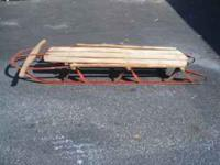 This antique wooden tobaggon sled has metal runners and