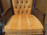 Yellow vintage chair with striped cushions and wood