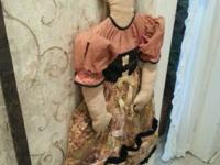 Vintage fabric doll with embroidered face holds little