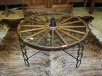 "WAGON WHEEL TABLE IS 36"" ROUND AND HAS A PIECE OF GLASS"
