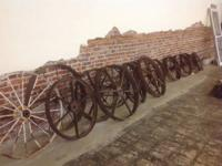 Wall of over 20 metal wheels varying in size from 24