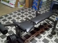 weight bench with arm and leg attachments and 2 bars.