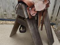 Old leather Western saddle on wooden sawhorse stand.