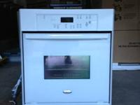 This is a white, electric wall oven made by whirlpool