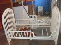 This is a white metal toddler bed in good condition.