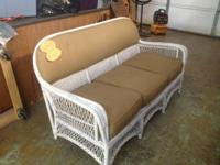 Strong developed white wicker sofa. Connected back
