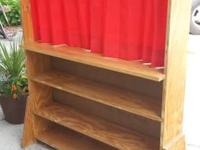 Custom made plywood puppet theater with red curtain.