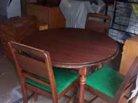 wooden round table has 4 wooden chairs. the table