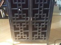 It is a very dark brown/black wooden cabinet. It has a