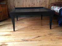 Large square wooden coffee table with black finish. In
