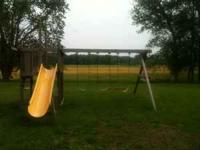Three swings and fort with slide. Missing fort cover.