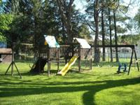 Large wooden swing set includes: rockwall, 2 slides (1