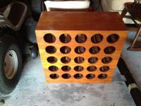 For sale is a wooden wine rack that holds 25 bottles.