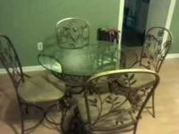 Wought Iron table with four chairs. Table top is glass