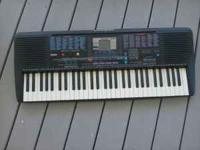 An electronic keyboard complete with stand, foot pedal